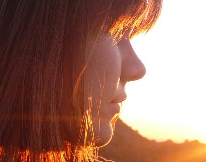 een vrouwen gezicht die in het zonlicht kijkt